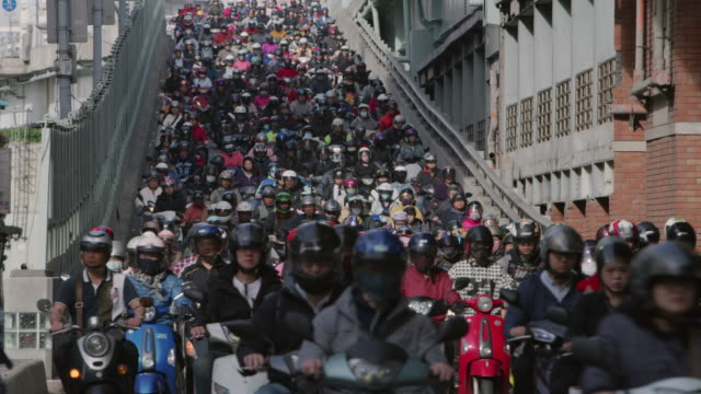ls a road crowded with motorcycles during rush hour / taipei, taiwan - 人口爆発点の映像素材/bロール