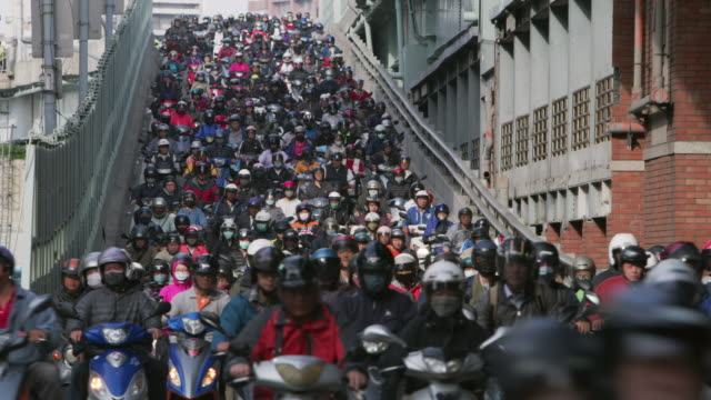 ls a road crowded with motorcycles during rush hour / taipei, taiwan - insel taiwan stock-videos und b-roll-filmmaterial