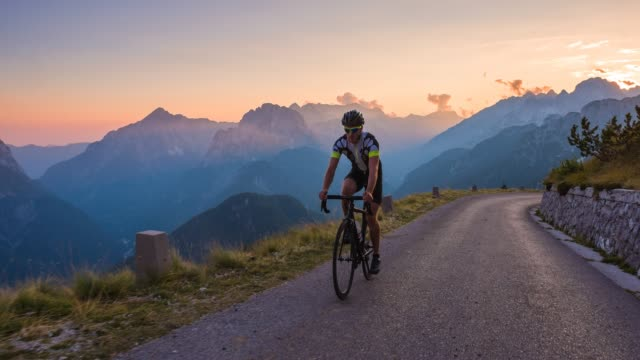 road cycling on a mountain pass at sunset - outdoor pursuit stock videos & royalty-free footage