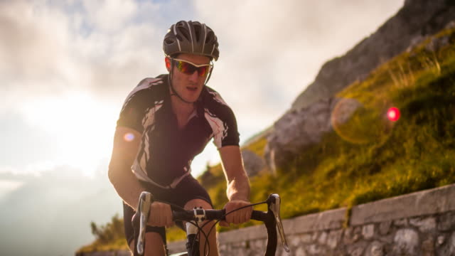 road cycling on a mountain pass at sunset - competitive sport stock videos & royalty-free footage