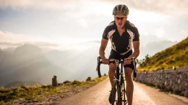 stockvideo's en b-roll-footage met road cycling on a mountain pass at sunset - uithoudingsvermogen