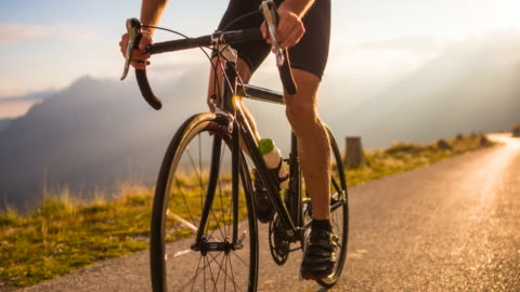 stockvideo's en b-roll-footage met road cycling on a mountain pass at sunset - cycling