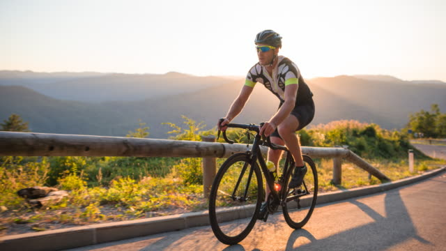 vídeos de stock e filmes b-roll de road cycling on a mountain pass at sunset - ciclismo