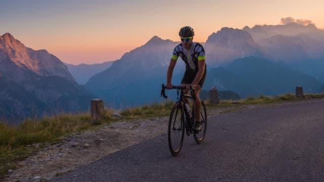vídeos de stock e filmes b-roll de road cycling on a scenic route at sunset, mountains in background - bicicleta de corrida