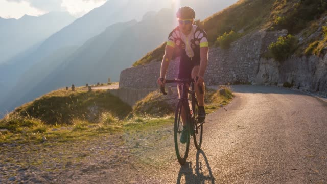 road cycling uphill a scenic mountain road, illuminated by sunlight - sports activity stock videos & royalty-free footage