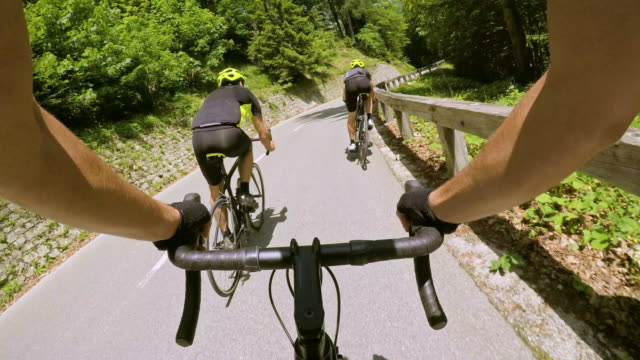 pov ciclismo su strada con due ciclisti maschi lungo una strada di montagna sotto il sole - point of view video stock e b–roll