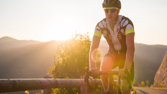 road cyclist cycling uphill at sunset - sports race stock videos & royalty-free footage