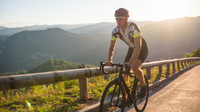 vídeos de stock e filmes b-roll de road cyclist cycling uphill on a beautiful sunny day - triatleta