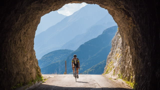 Road cyclist going into a rocky tunnel in mountains