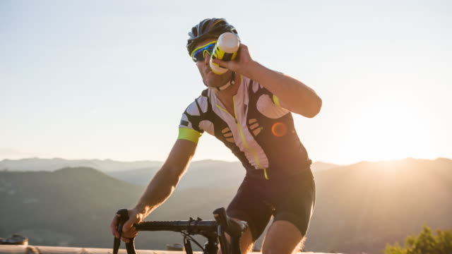 road cyclist hydrating while pushing his limits cycling uphill - sport video stock e b–roll
