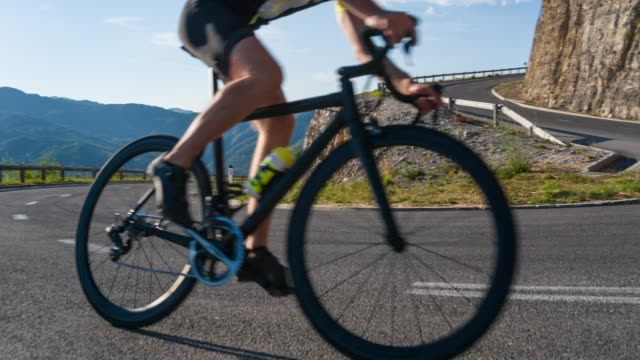 road cyclist making a turn on a winding road - mountain pass stock videos & royalty-free footage