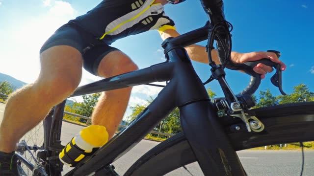 vidéos et rushes de cycliste de route pédalant, vélo en montée sur une journée ensoleillée en été - qui monte