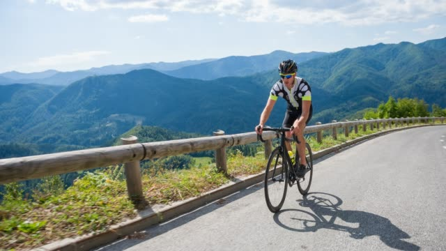 road cyclist pedaling uphill on mountain pass - steep stock videos & royalty-free footage