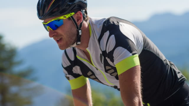 road cyclist pedalling uphill - sunglasses stock videos & royalty-free footage