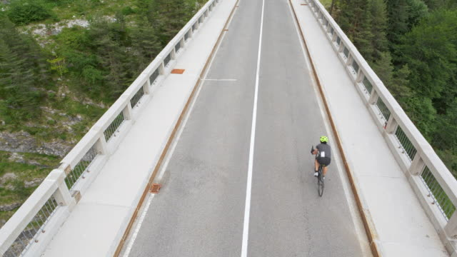 aerial road cyclist speeding across a bridge high in the mountains - road marking stock videos & royalty-free footage
