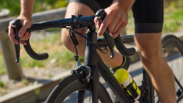 上り坂をサイクリングしながらハンドルをしっかりつかむロードサイクリスト - 競争点の映像素材/bロール
