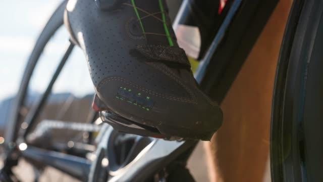 vídeos de stock e filmes b-roll de road cyclist unclipping cycling shoes out of road bike pedal - bicicleta de corrida