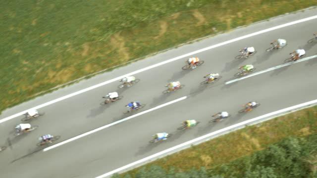 vidéos et rushes de aerial cyclistes de route de course sur une route de montagne - vue en plongée