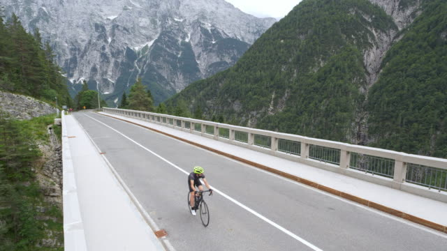 aerial road cyclists riding across a nice bridge high in the mountains - road marking stock videos & royalty-free footage