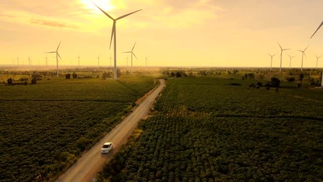 straße auf der grünen wiese mit windkraftanlagen und sonnenuntergang hintergründe - generator stock-videos und b-roll-filmmaterial