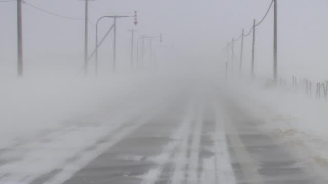 road in the snowstorm, hokkaido, japan - empty road stock videos & royalty-free footage