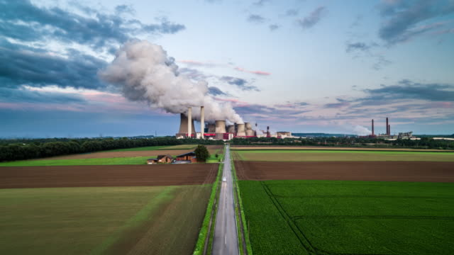 aerial: road leading to coal fired power station - smoke stack stock videos & royalty-free footage