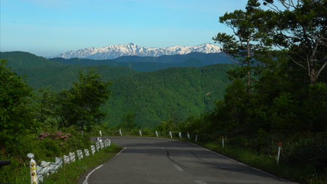 road leading towards snow capped mountains - plusphoto stock videos & royalty-free footage