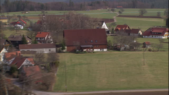 A road leads past a small village with farmhouses, fields and a small church in the German countryside.