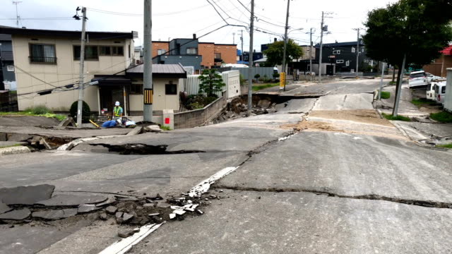 a road lies heavily damaged after being struck by an earthquake on september 7 2018 in kiyota near sapporo japan sixteen people are now known to have... - erdbeben stock-videos und b-roll-filmmaterial