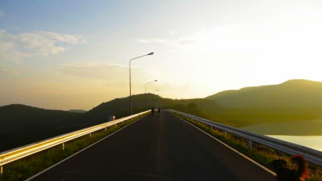 vídeos de stock, filmes e b-roll de a estrada nas proximidades do lake ao pôr-do-sol - ângulo agudo