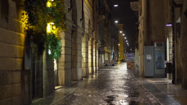 a road of verona under the rain at night - kopfsteinpflaster stock-videos und b-roll-filmmaterial