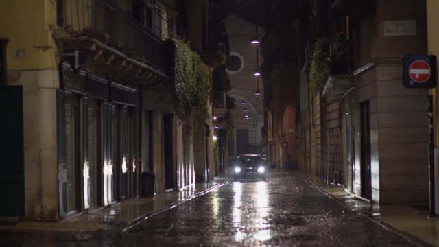 road of verona with incoming car during a rainy night - altstadt stock-videos und b-roll-filmmaterial