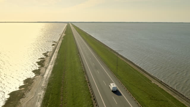AERIAL Road on a dam across a sea at sunset