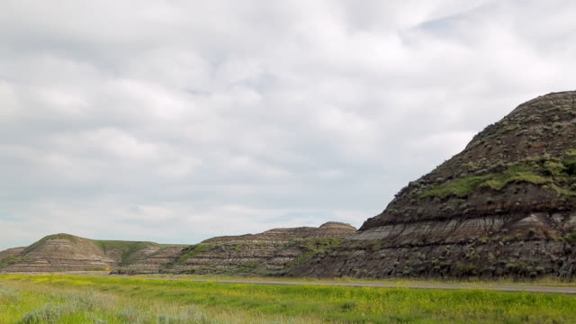 A road pass by the rock formation of the Badlands in Canada