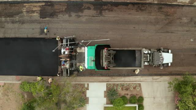 住宅街の時間経過に道路舗装-空中ドローンショット - ダンプカー点の映像素材/bロール