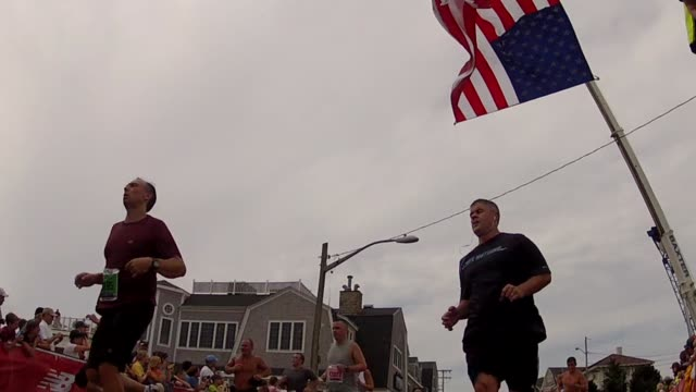 stockvideo's en b-roll-footage met road racing the great american road race an annual event on cape cod along martha's vineyard sound runners under american flag at finish line - salmini