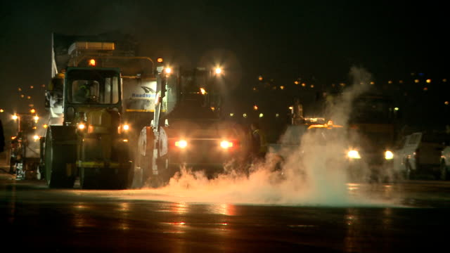 ws pan road resurfacing machines on a construction site at night, cape town, south africa - 建設機械点の映像素材/bロール