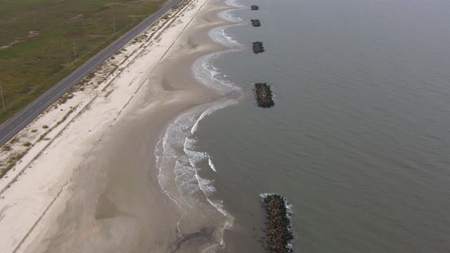 A road runs beside a rocky beach.