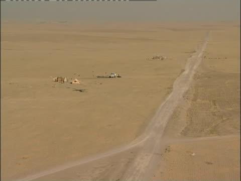 A road runs next to a Bedouin sheep camp.