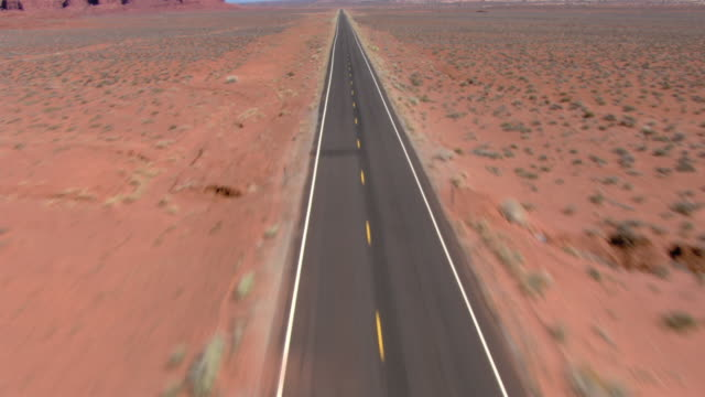 a road runs straight through the desert toward bluffs. - empty road stock videos and b-roll footage