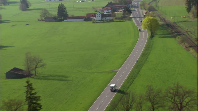 a road runs through a green valley past farms and homes. - romantic road germany stock videos and b-roll footage