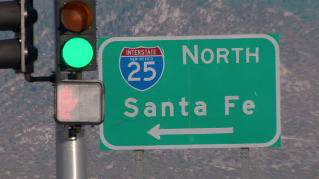 a road sign at an intersection points the way to i-25 and santa fe. - verkehrsschild stock-videos und b-roll-filmmaterial