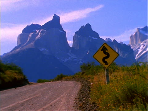 road sign beside dirt road with mountains in background / chile / torrie del paine - segnaletica stradale video stock e b–roll