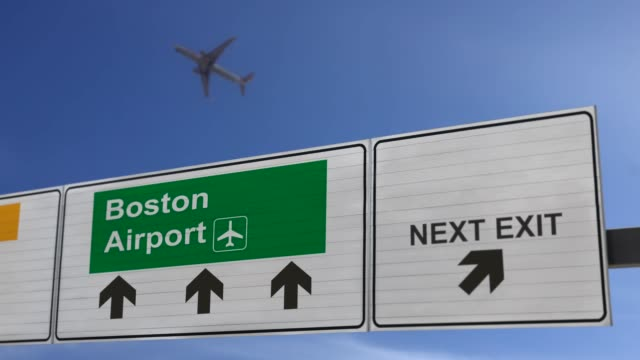 road sign indicating the direction of boston airport and a plane that just got up. - boston massachusetts stock videos & royalty-free footage