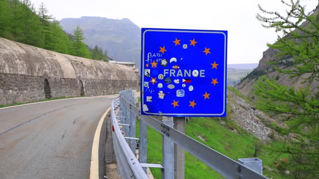 road sign materializes the entrance to france from italy at the mont cenis pass on june 3 in val cenis, france. from june 9, the flow of travelers... - mountain range stock videos & royalty-free footage
