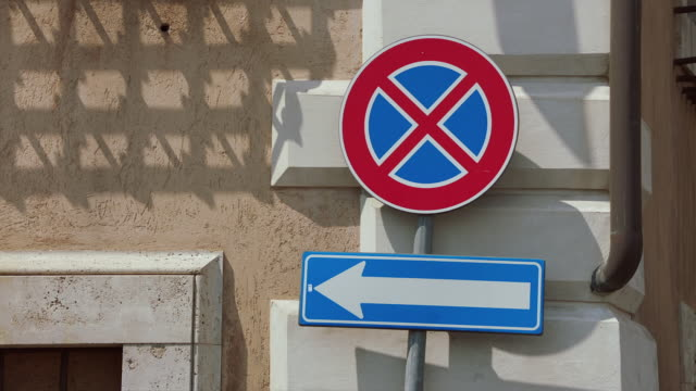 MS Road sign on pole against wall / Rome, Italy