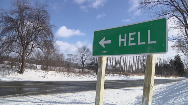 MS Road sign pointing to 'Hell' along snowy country roadside / Chelsea, Michigan