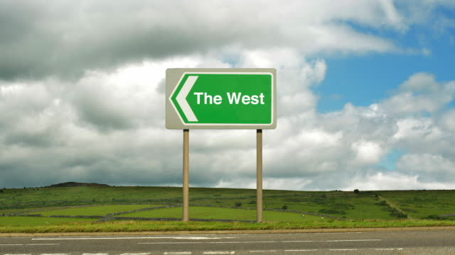 road sign to the west. - gruppo medio di animali video stock e b–roll
