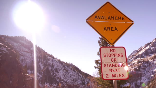 vídeos y material grabado en eventos de stock de a road sign warns of an avalanche area on a snowy mountain road in colorado. - señal de advertencia
