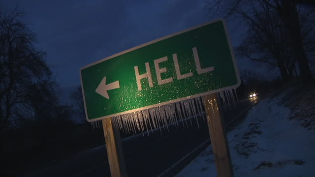 CU Road sign with icicles pointing to 'Hell' at night / car passes by / Chelsea, Michigan
